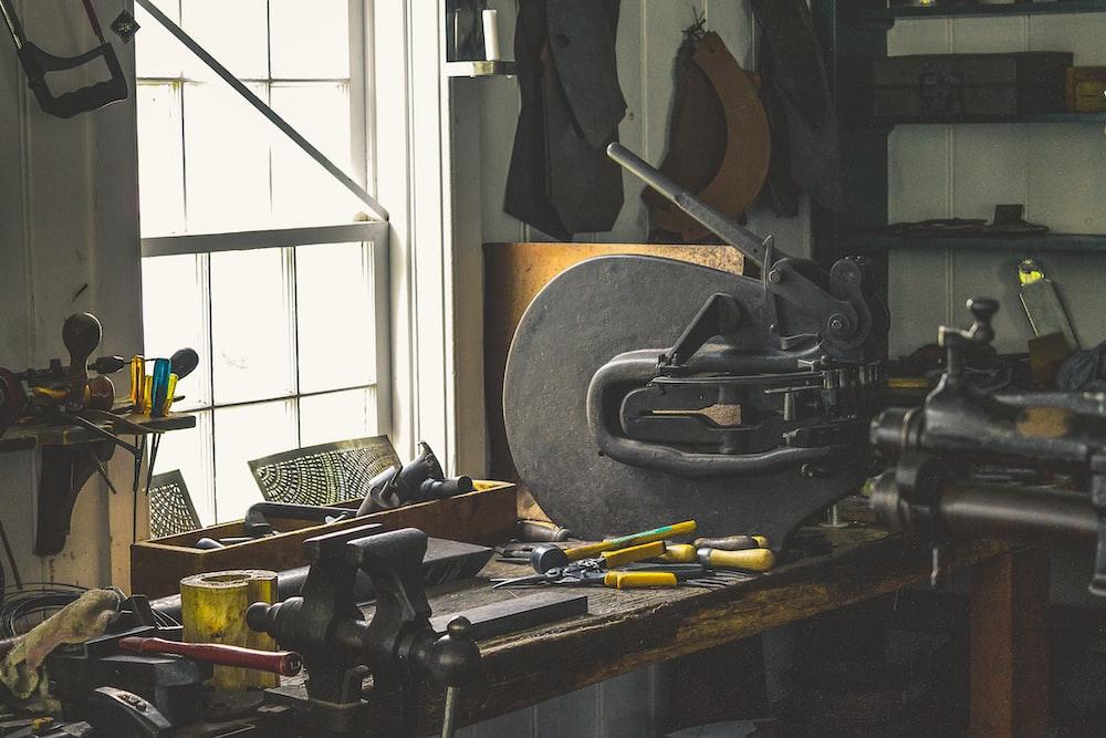 black bench vise on brown wooden work bench