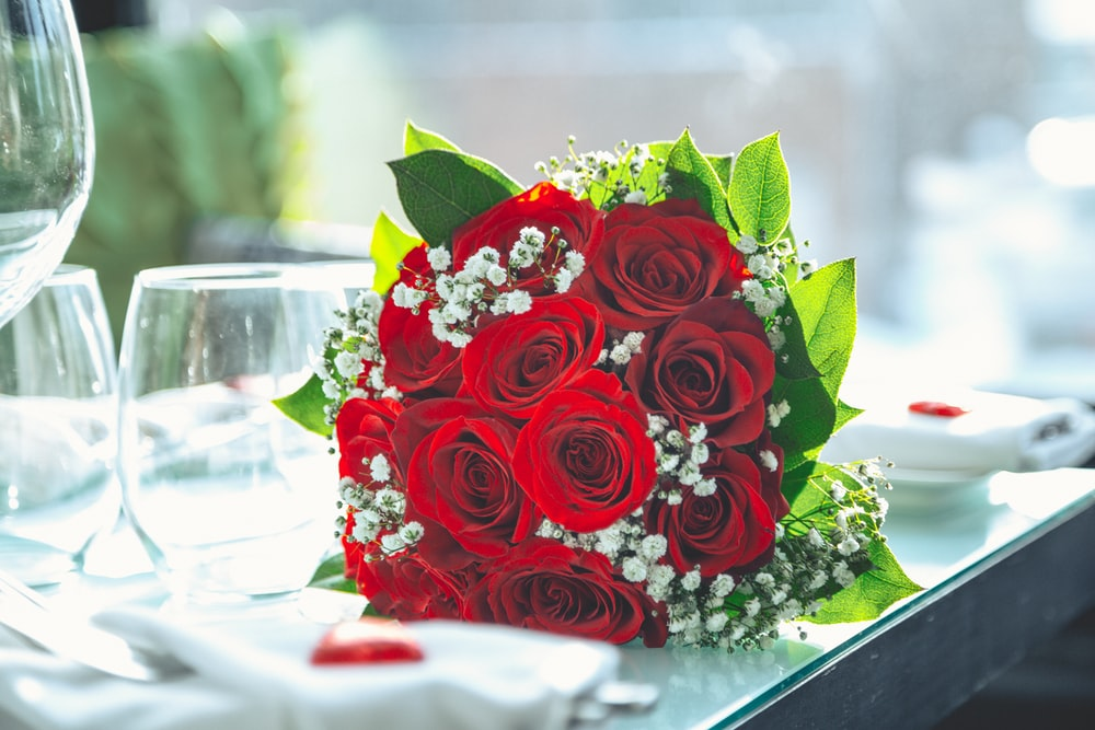 rose bouquet on table beside empty drinking glasses