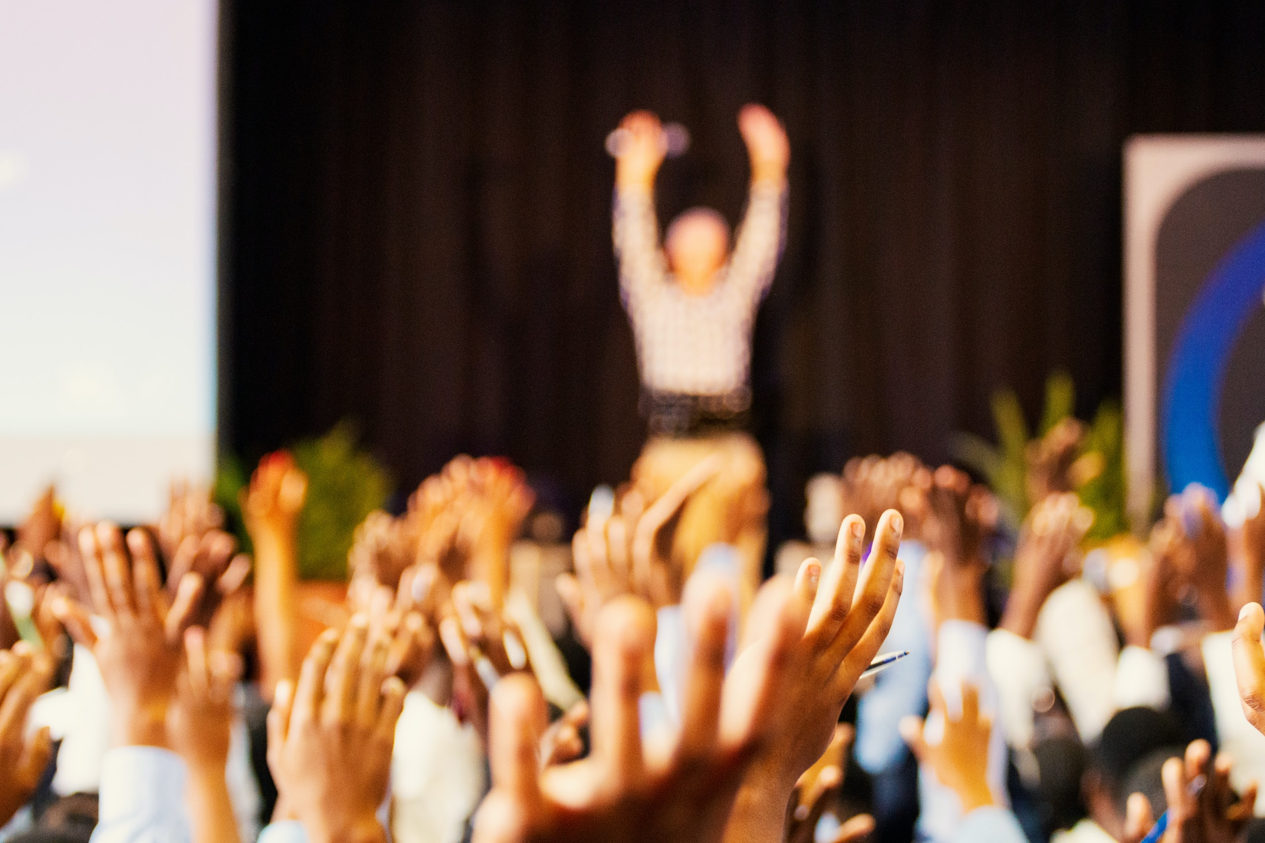 people raising hands with bokeh lights