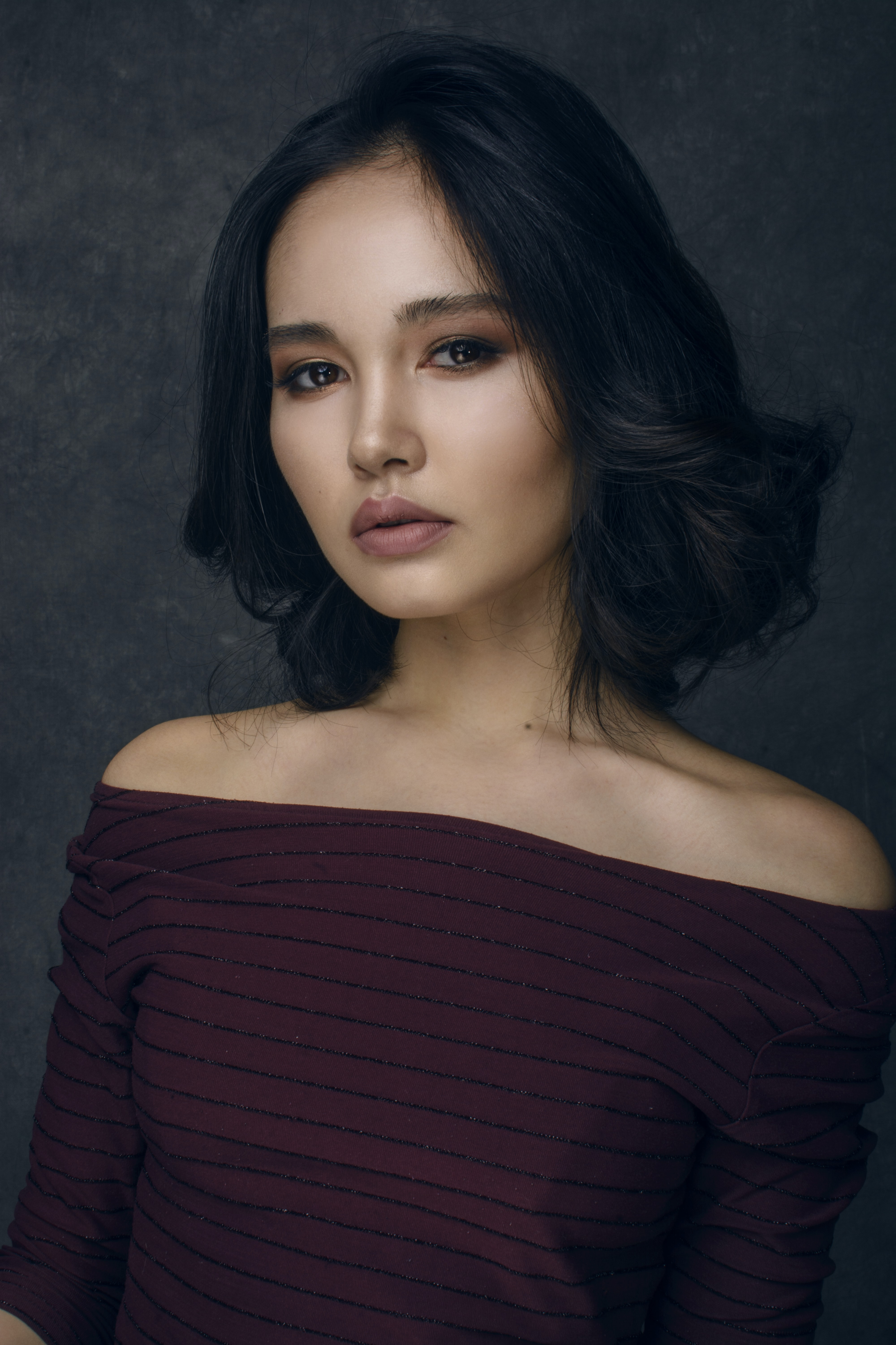 selective focus photography of woman wearing maroon striped off-shoulder shirt