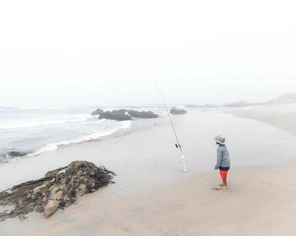 standing boy near seashore under cloudy sky