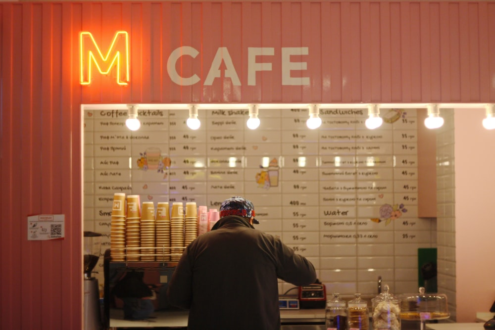 man standing in front of M Cafe store