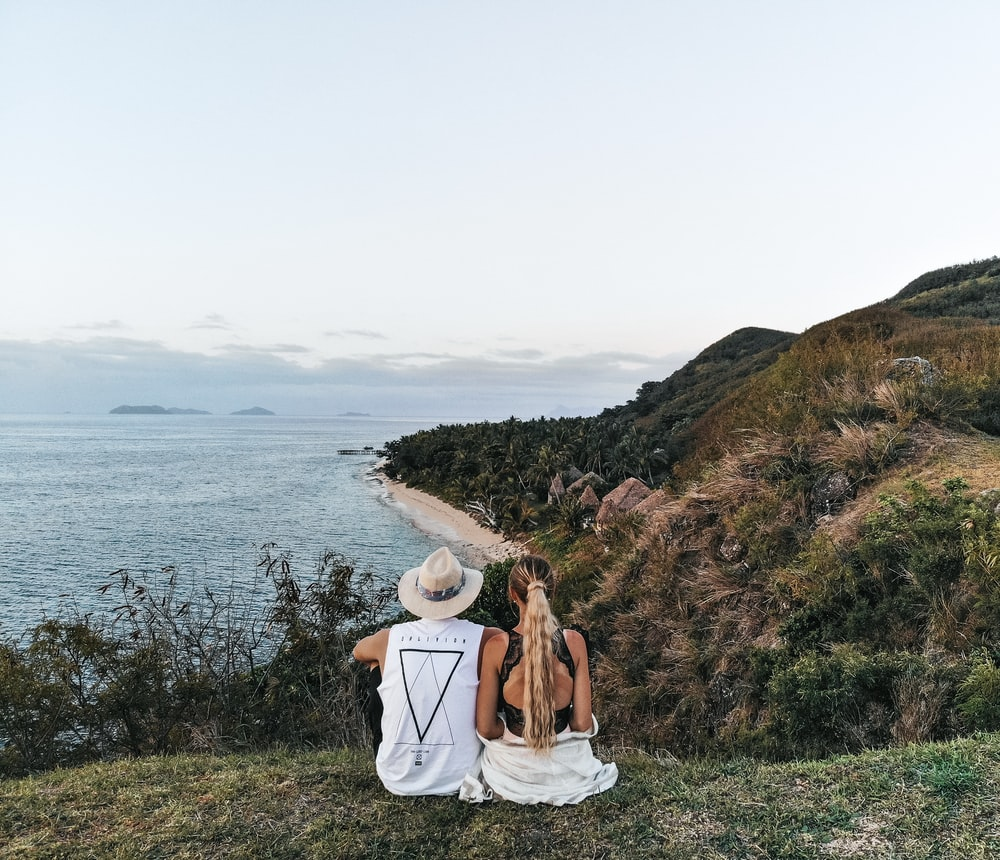 couple sitting on hill near body of water