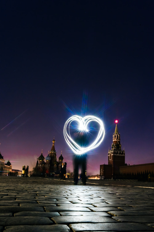 man forrming heart light