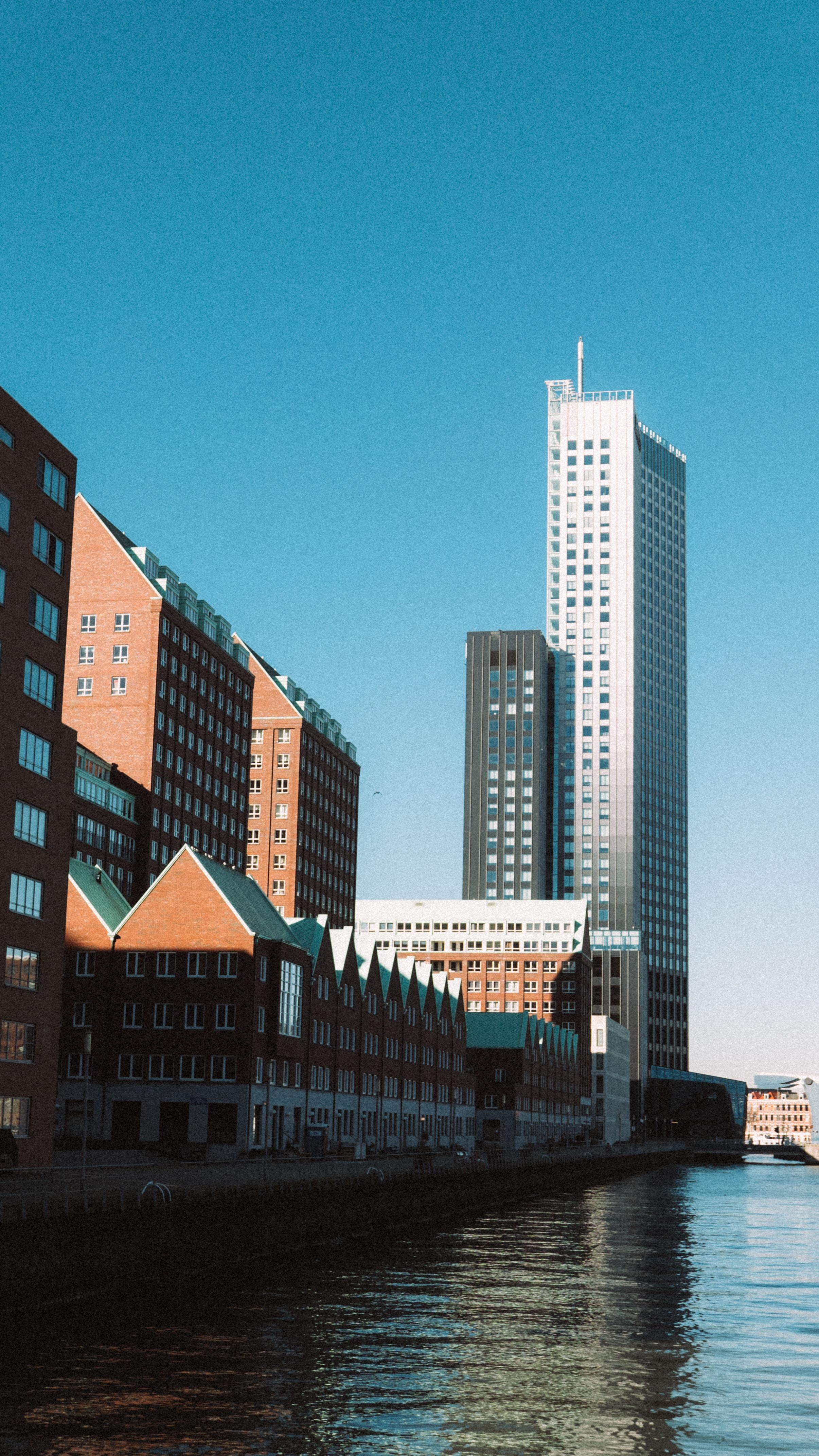 buildings beside body of water under clear blue sky