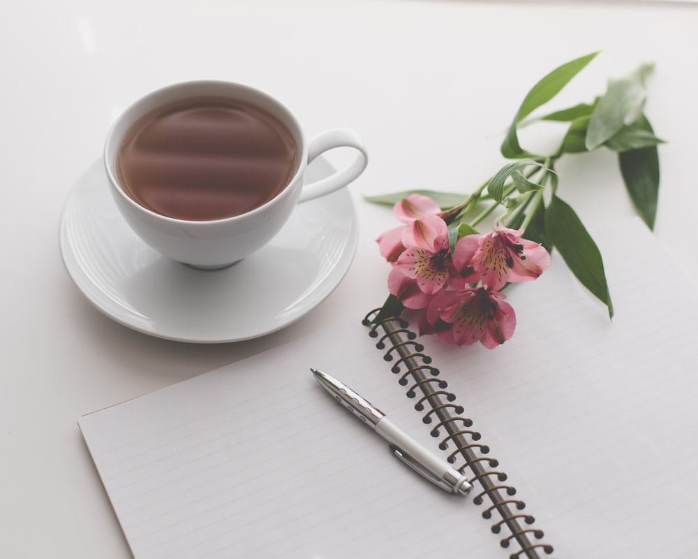white teacup filled with brown liquid near pink flower