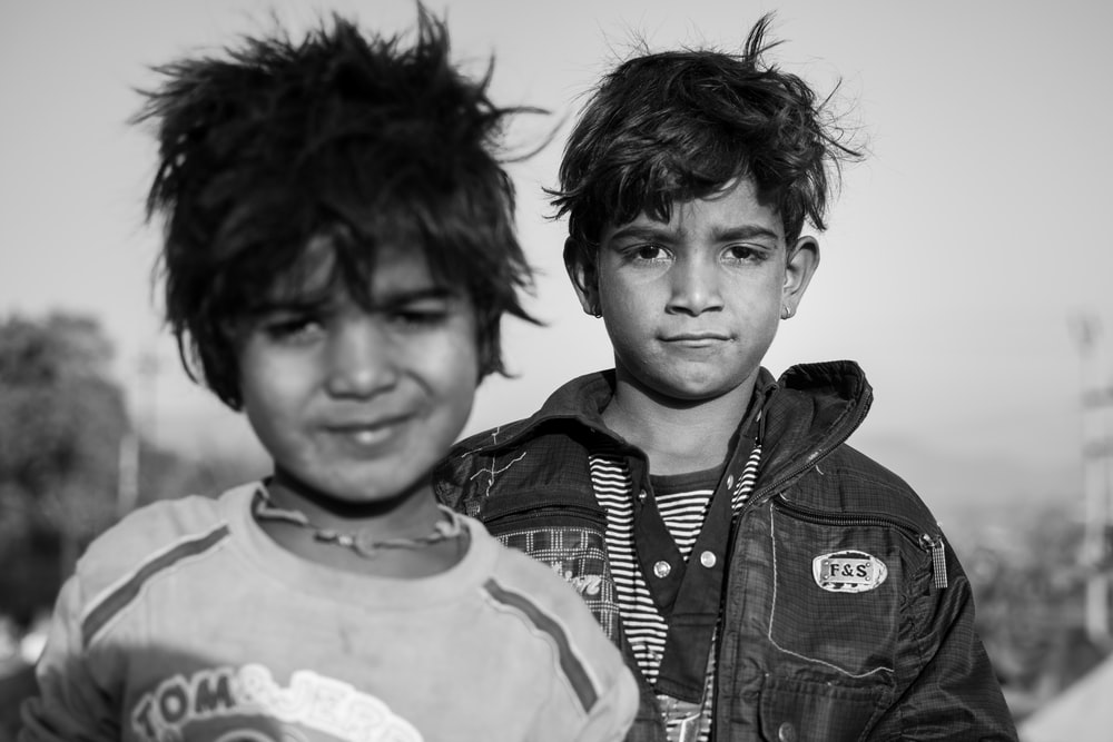 grayscale photography of two boys