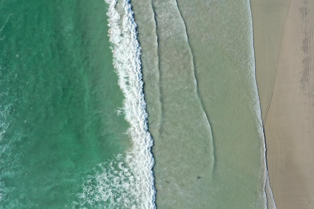 waves bashing on shore during daytime