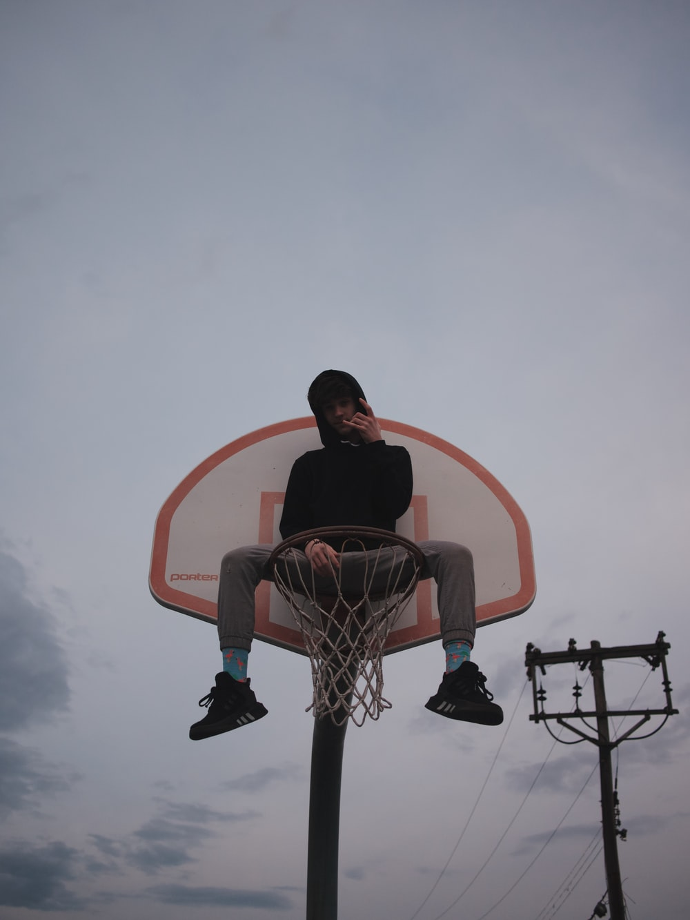 man sitting on red and white basketball hoop