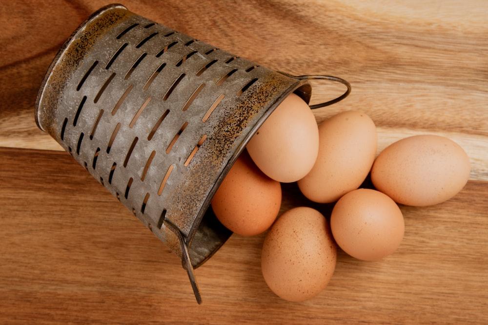 beige egg on gray steel bucket