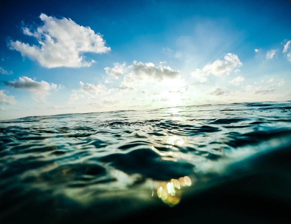 white clouds in blue sky over calm sea