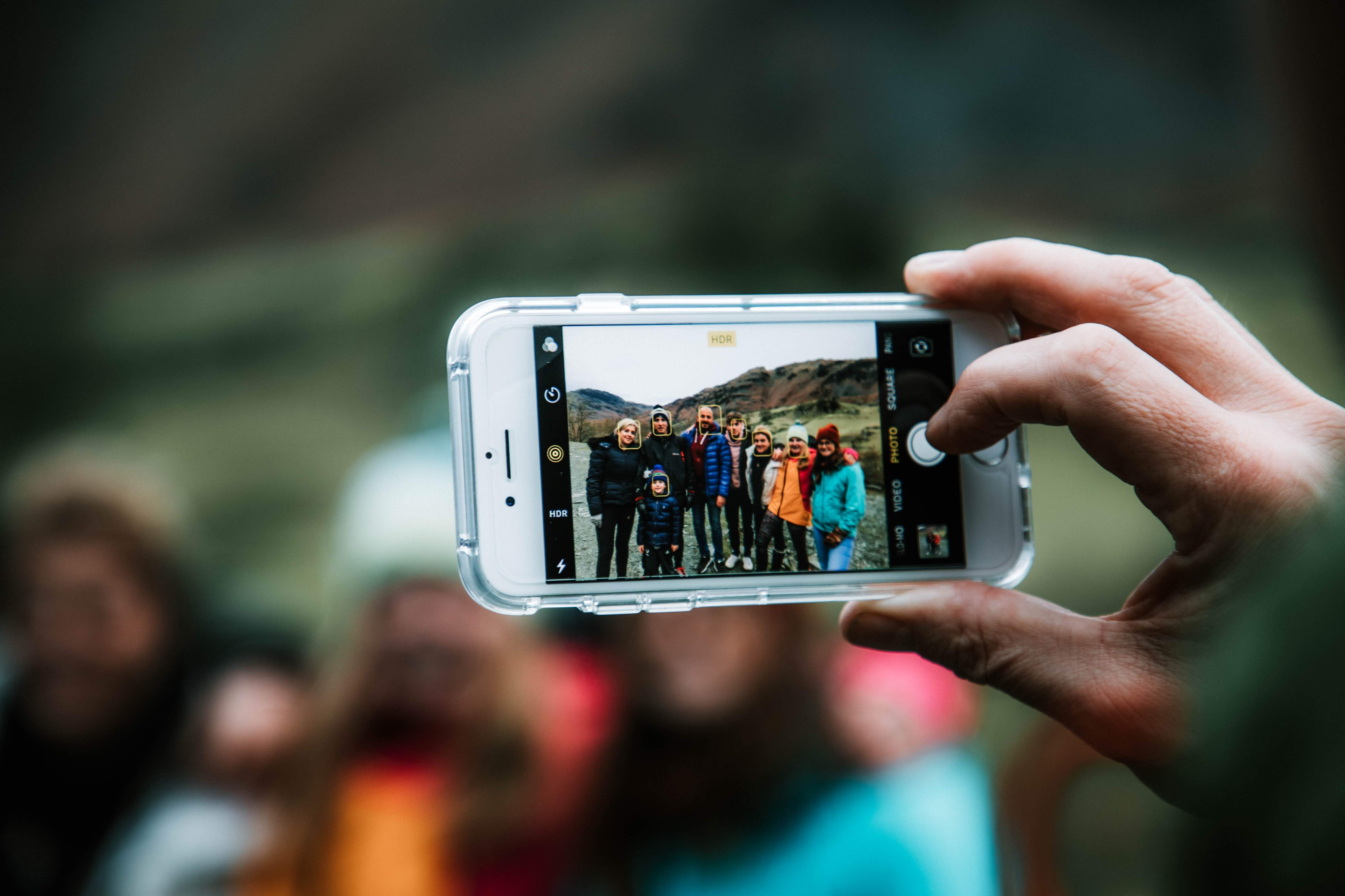 person holding silver iPhone 6 taking photo of people