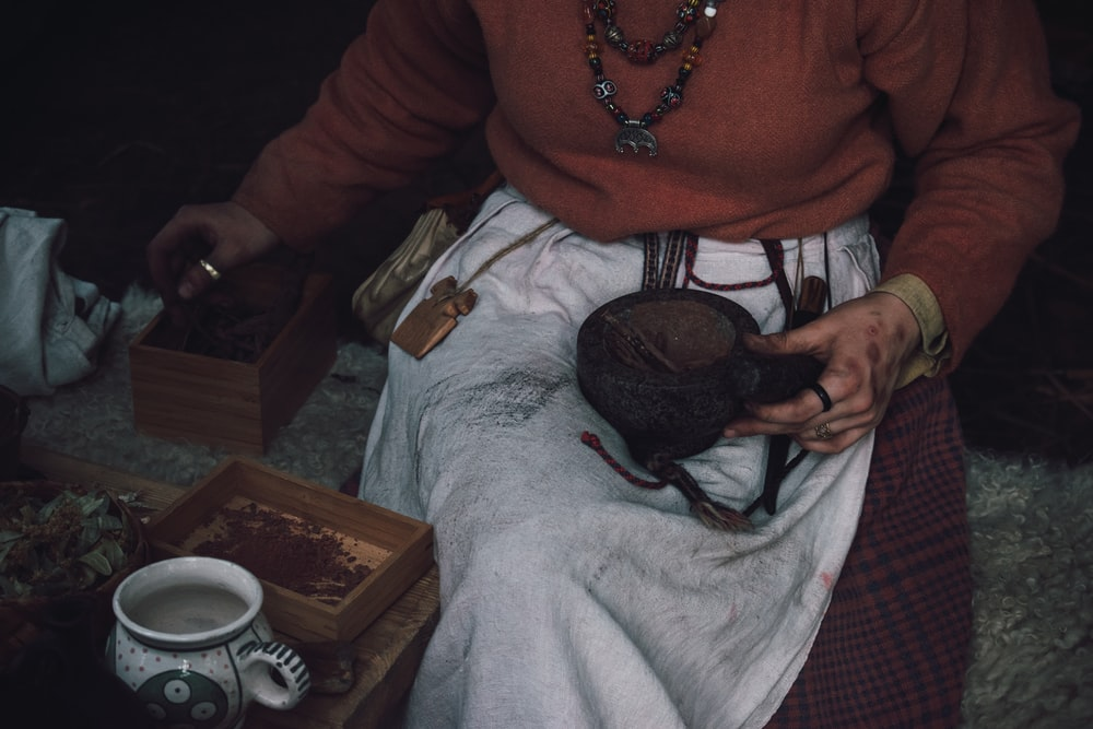 person in red sweater sits beside table with white tea cup