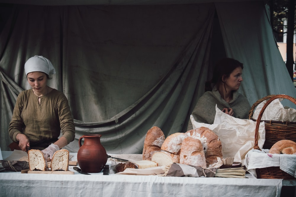 woman slicing bread beside woman standing beside basket