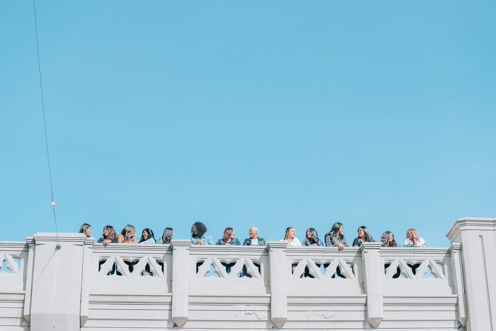 women standing in front of handrail