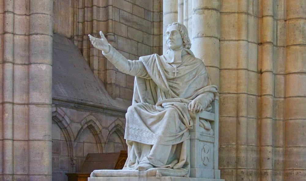 gray concrete man sitting statue