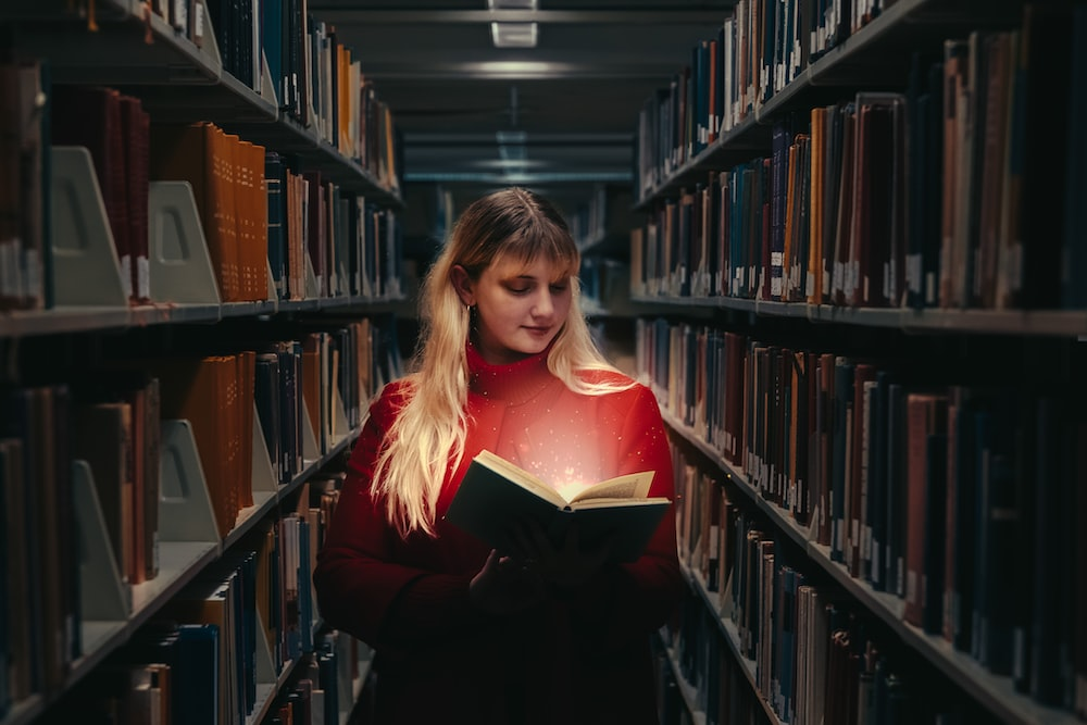 woman in red turtleneck sweater holding book between library shelves