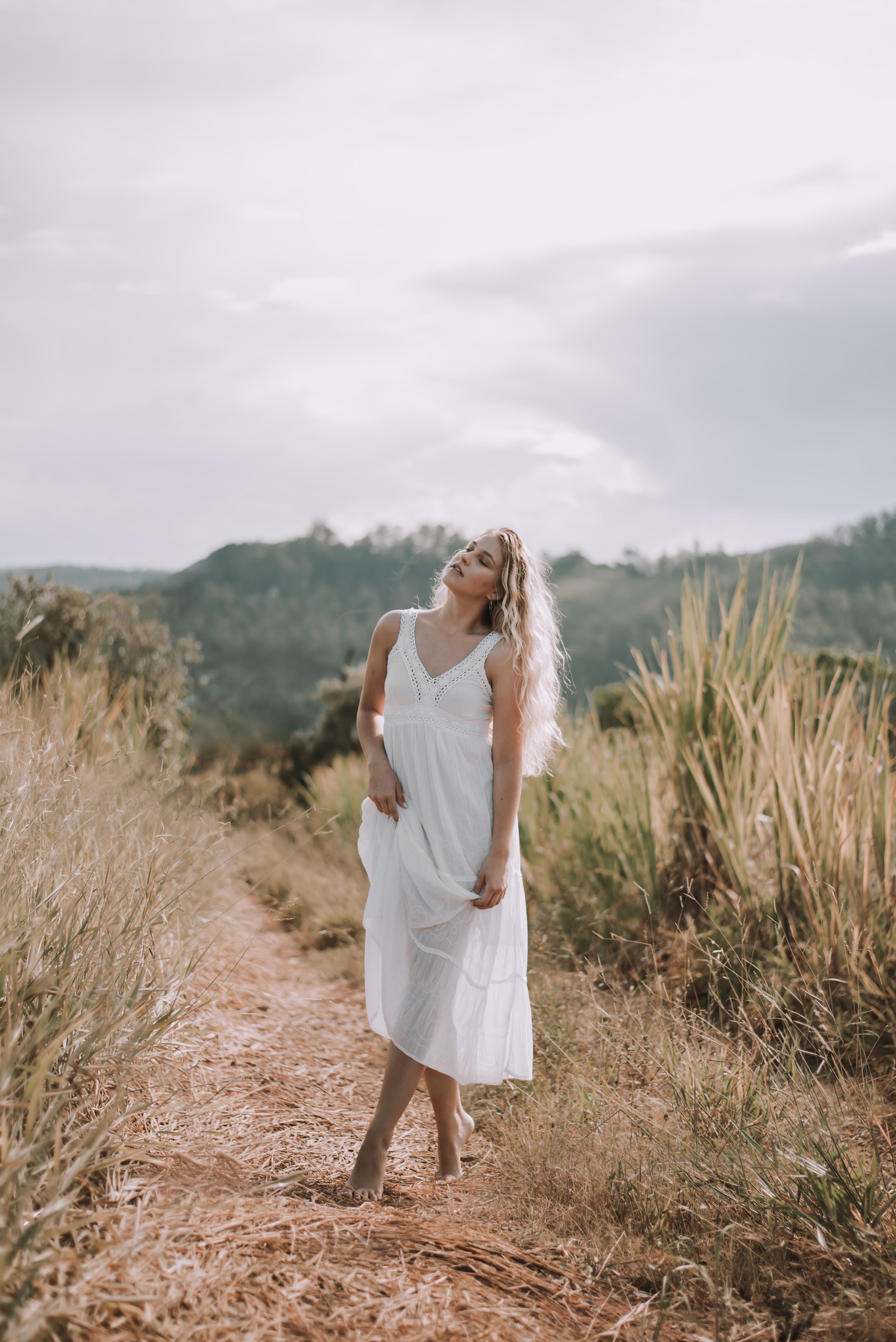 standing woman wearing white sleeveless dress during daytime