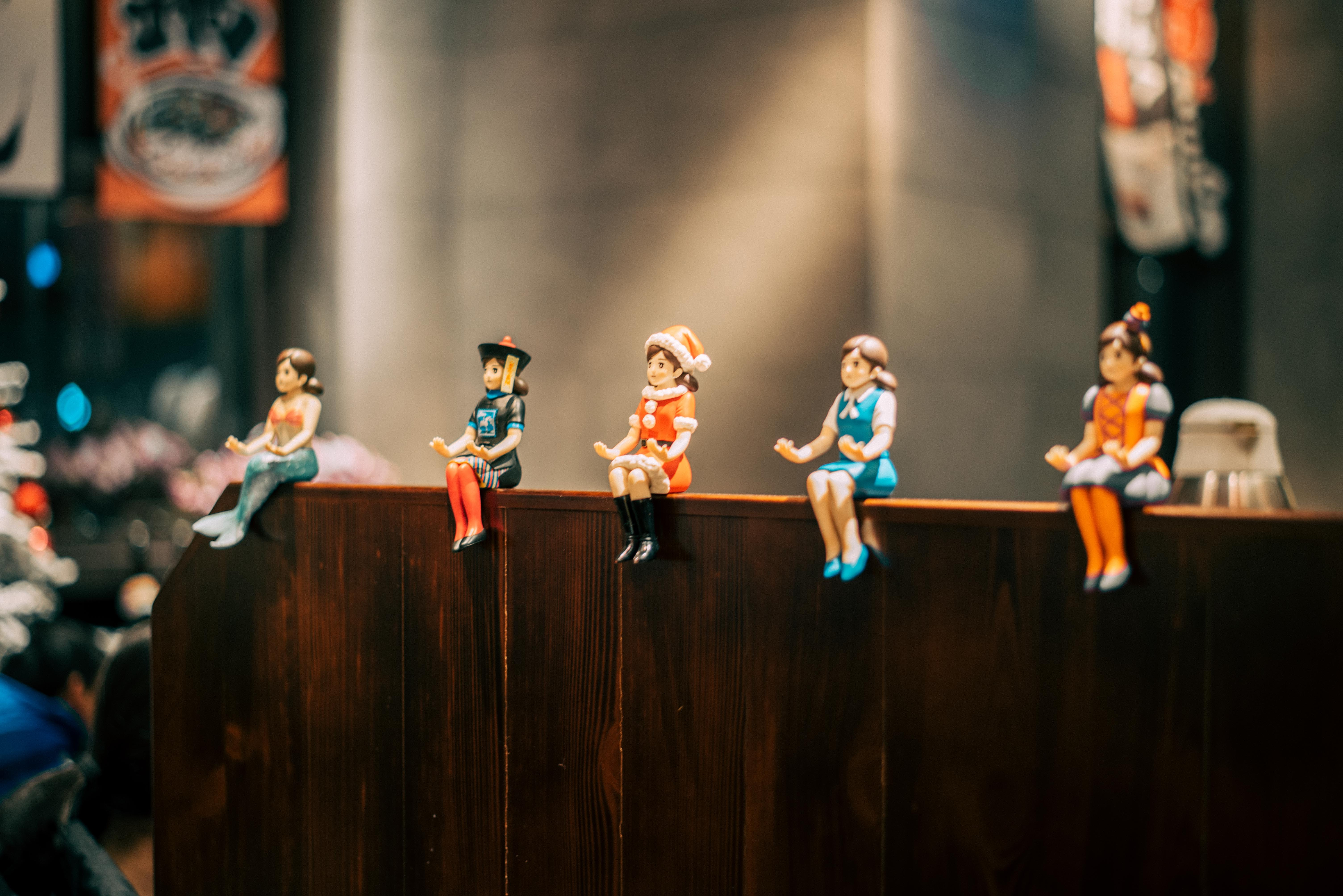 women action figures sits on brown wooden panel