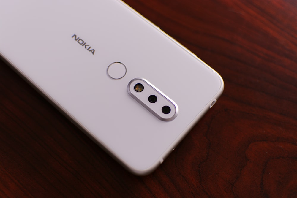 white Nokia smartphone on brown surface