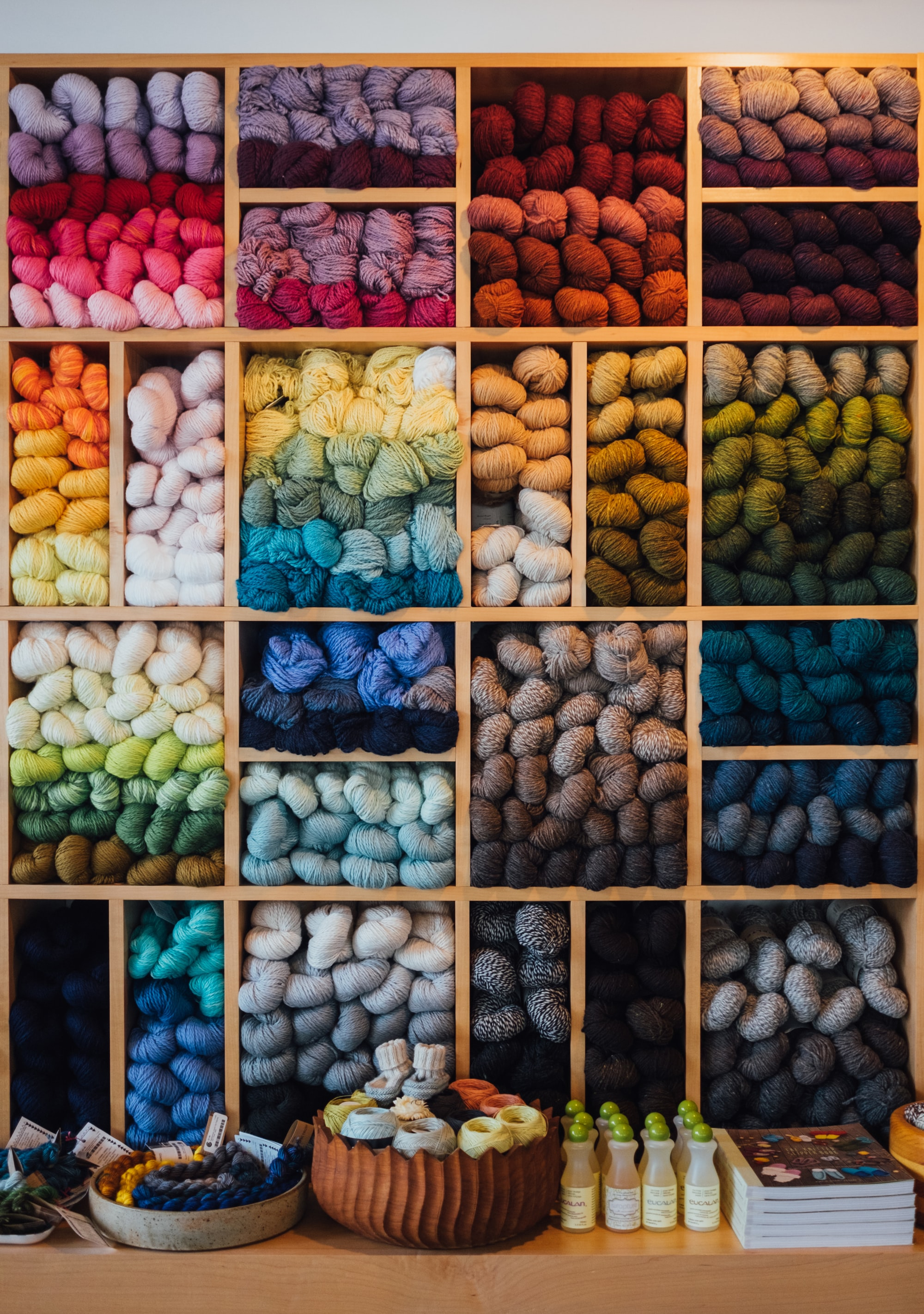 A bunch of different colors of yarn, sorted by color, sit bundled in cubbies.