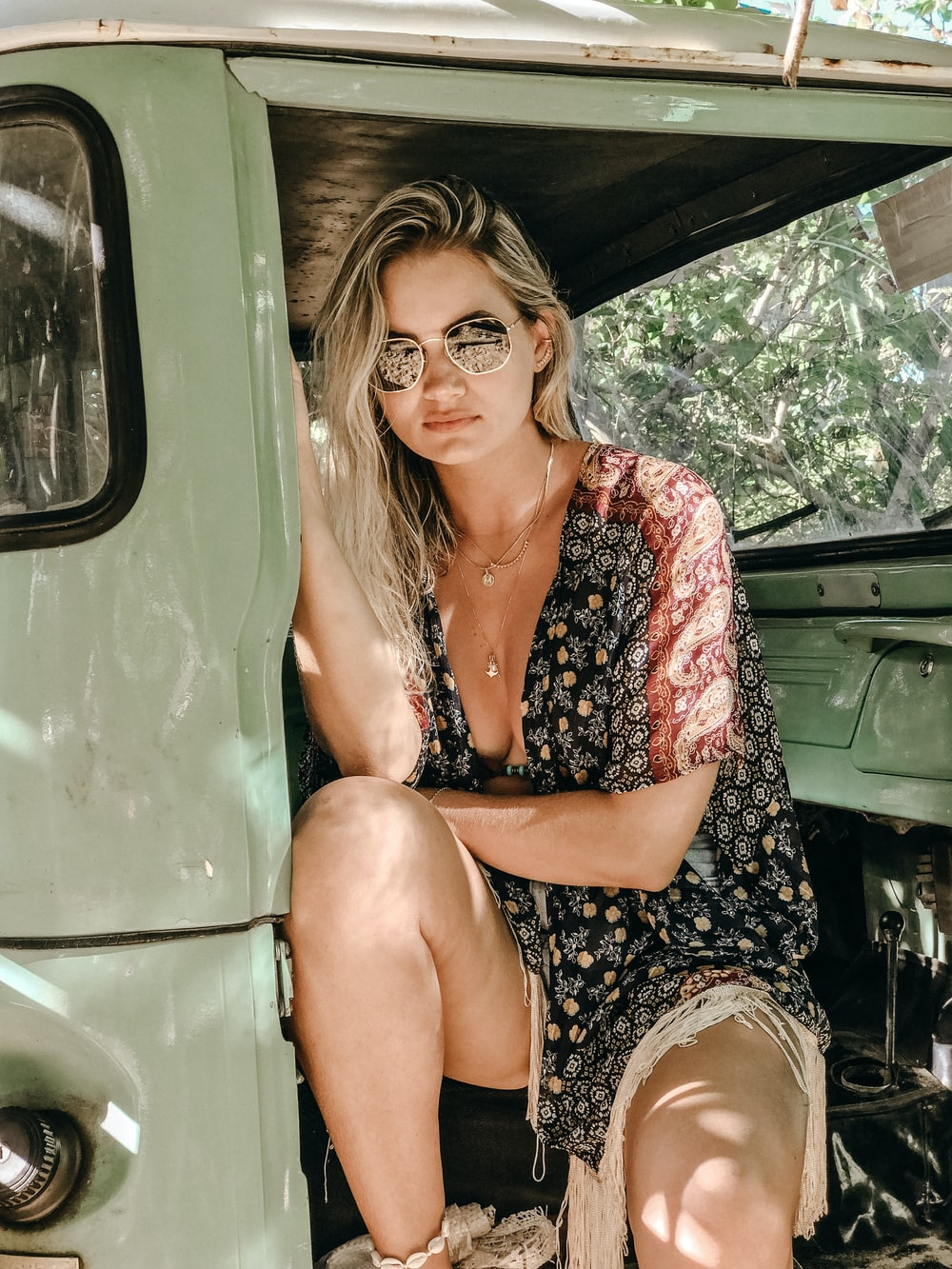 woman wearing floral dress and sunglasses sitting on vehicle