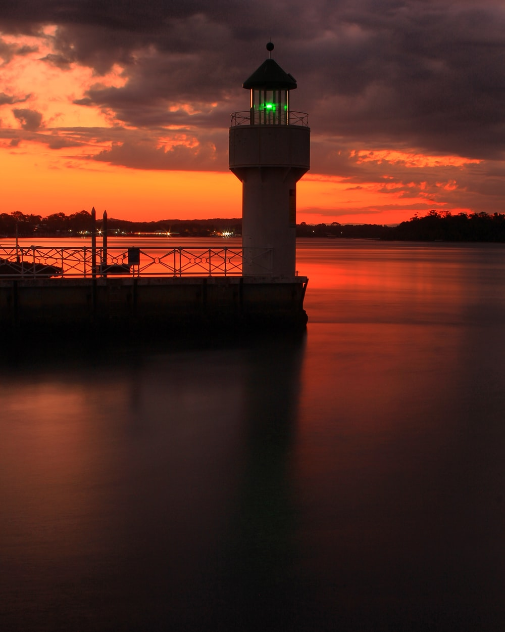 red and black sky and a lighthouse