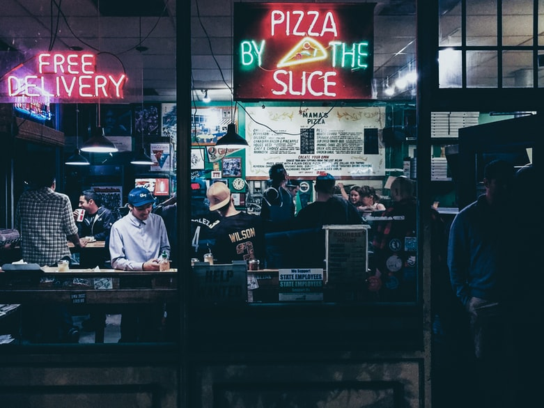 pizza by the slice neon sign hanged on glass panel