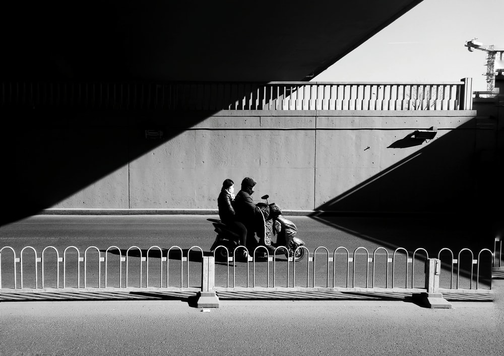 grayscale photo of two person sitting near fence