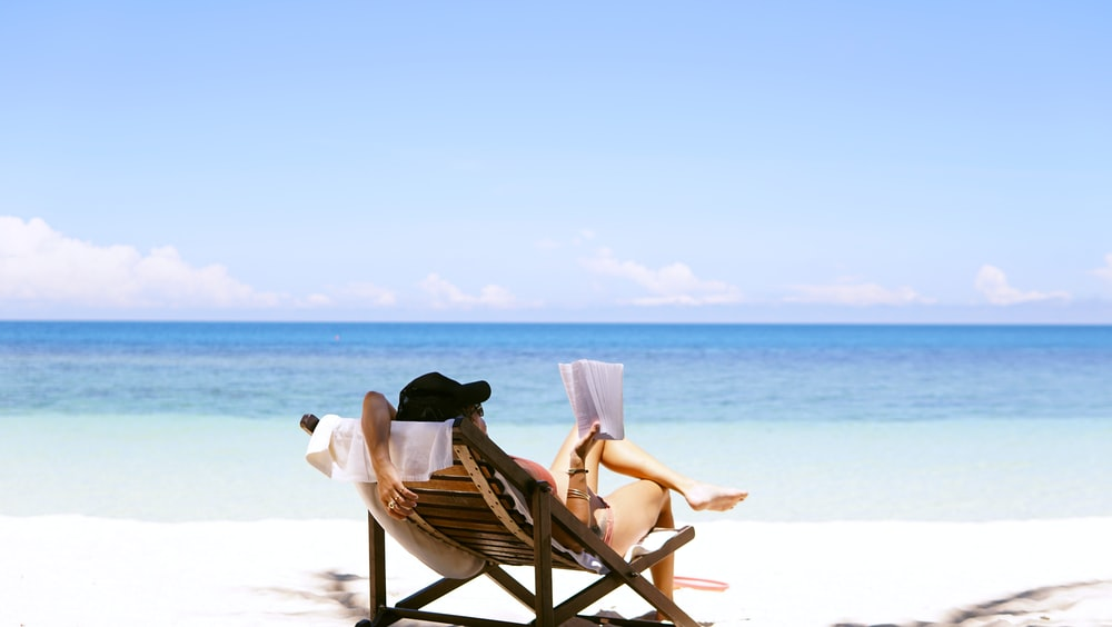 woman sits on brown wooden beach chair