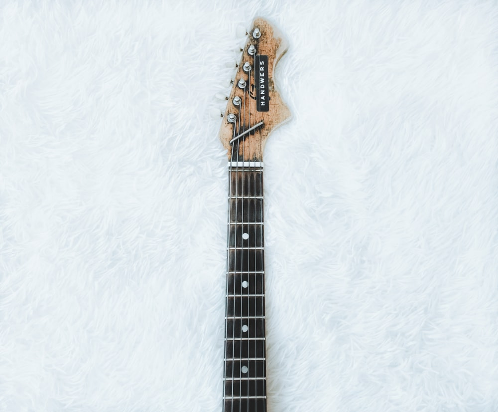 top view of electric guitar neck and headstock on white faux fur