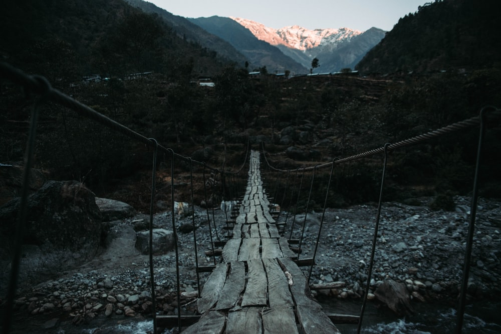 wooden floor hanging bridge above rocky river