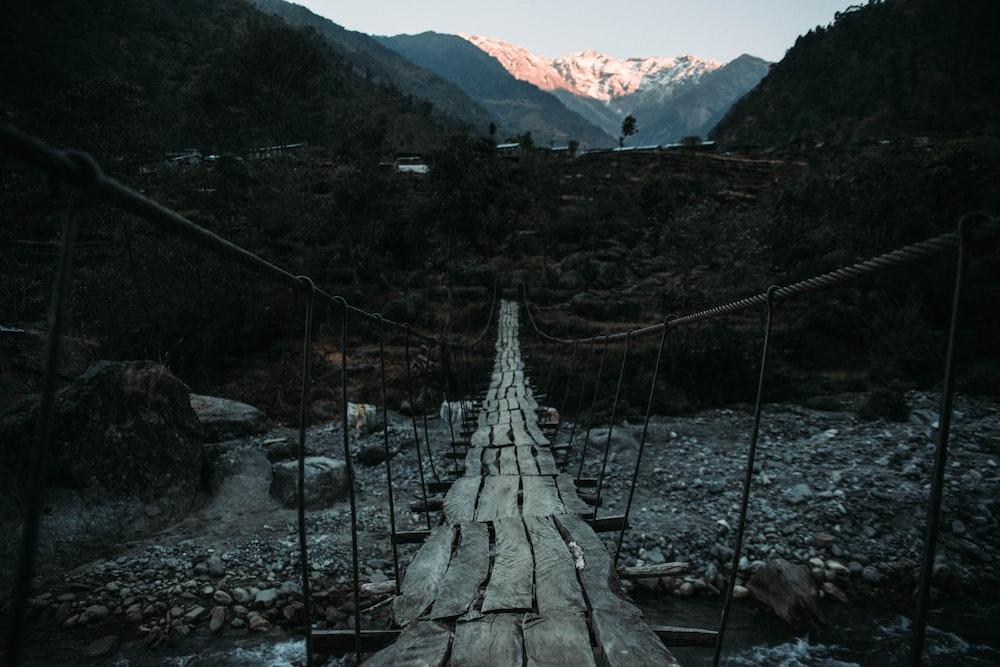 wooden floor hanging bridge above rocky river