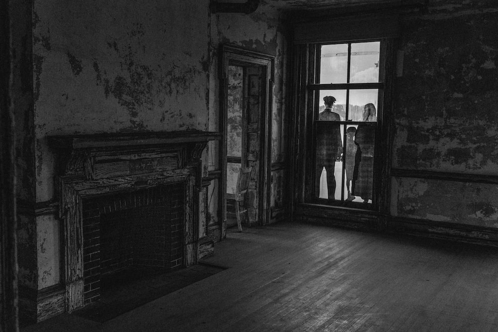 three person standing outside closed door