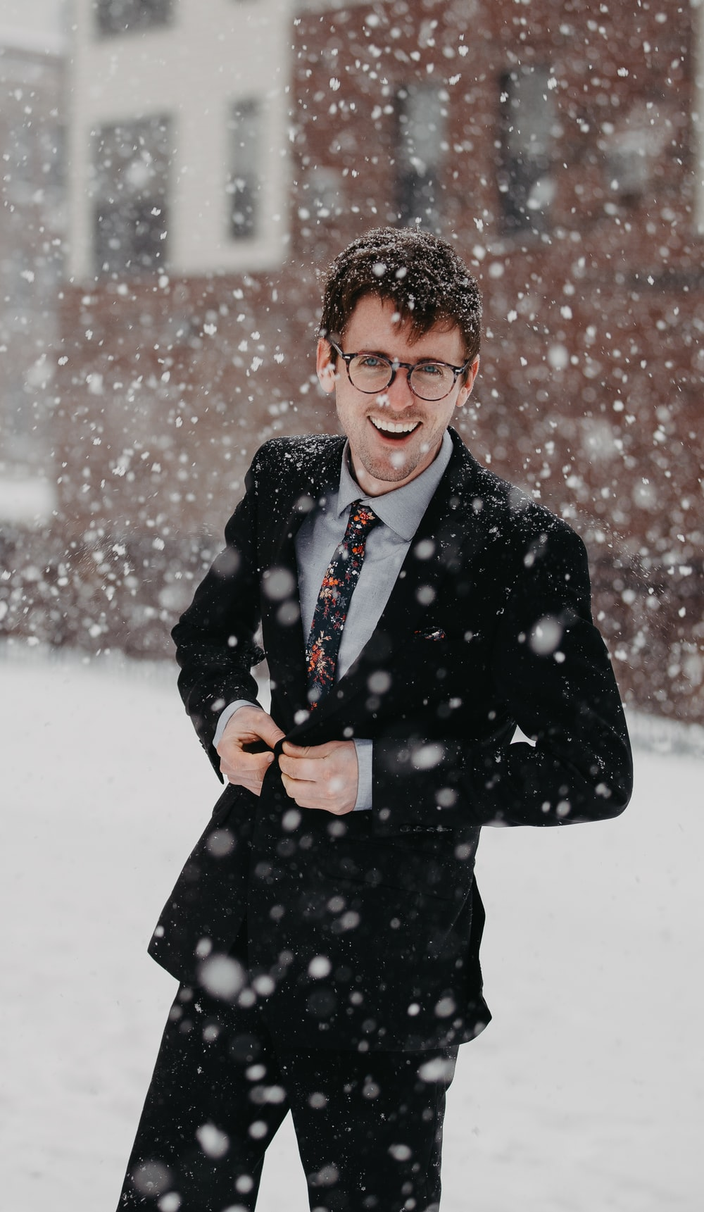 man wearing black suit under snow