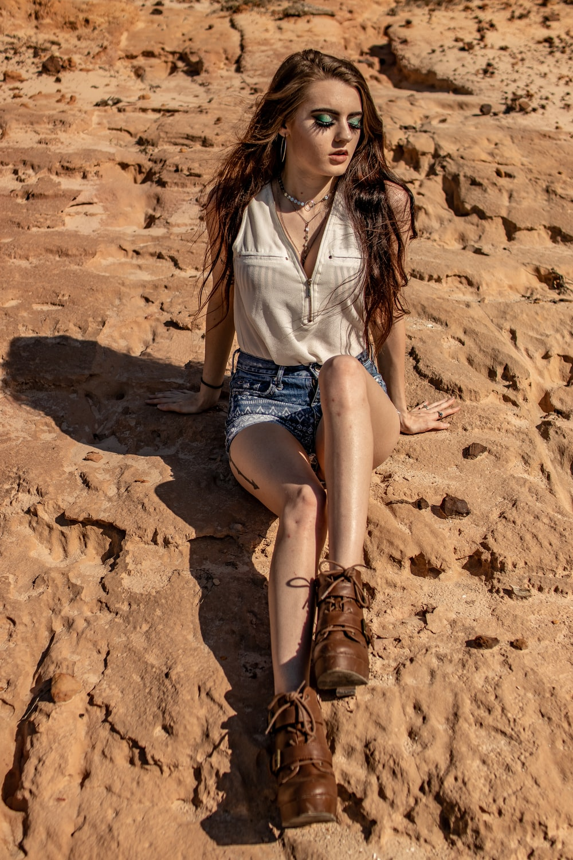 woman sitting on rock during daytime