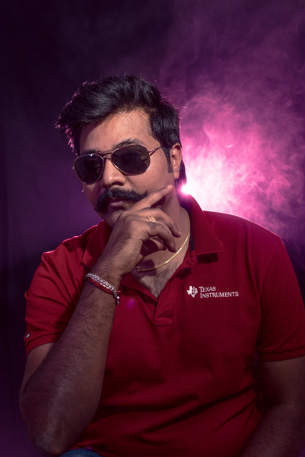 man wearing red polo shirt and black-framed Aviator-style sunglasses