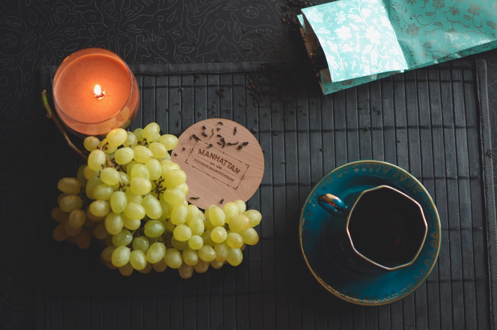 green grapes beside ceramic teacup