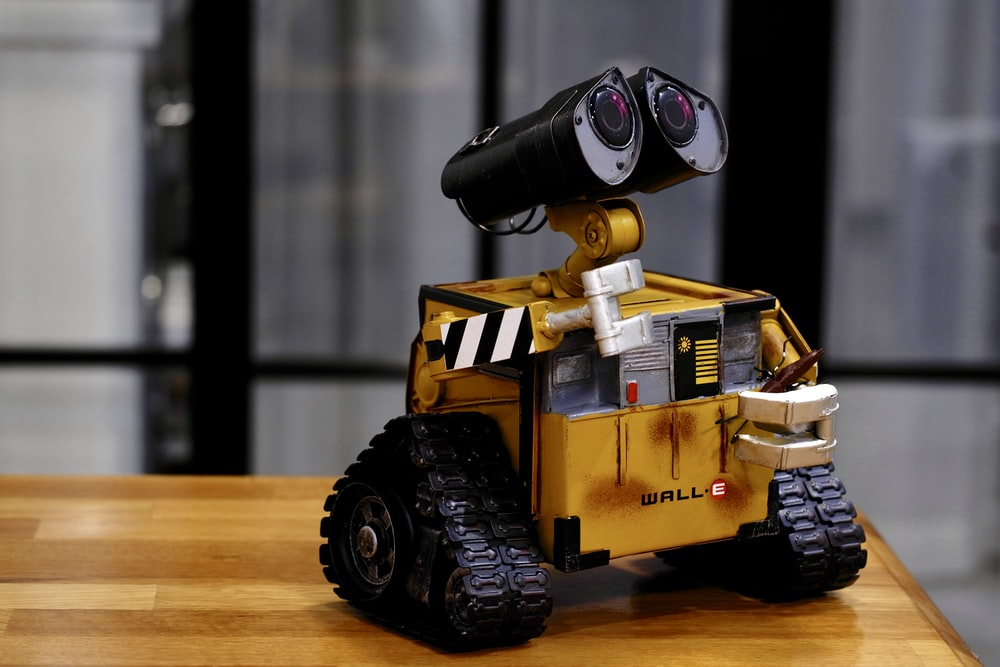 yellow and black Wall-E toy on brown wooden table