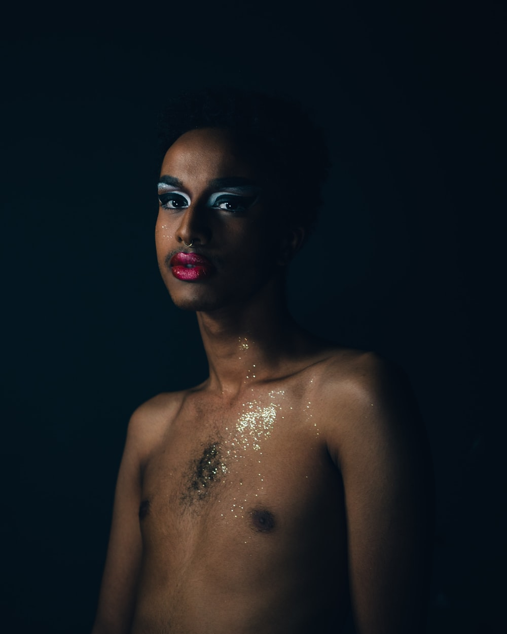 man with pink lipstick and highlighted eyeshadow inside dim lighted room