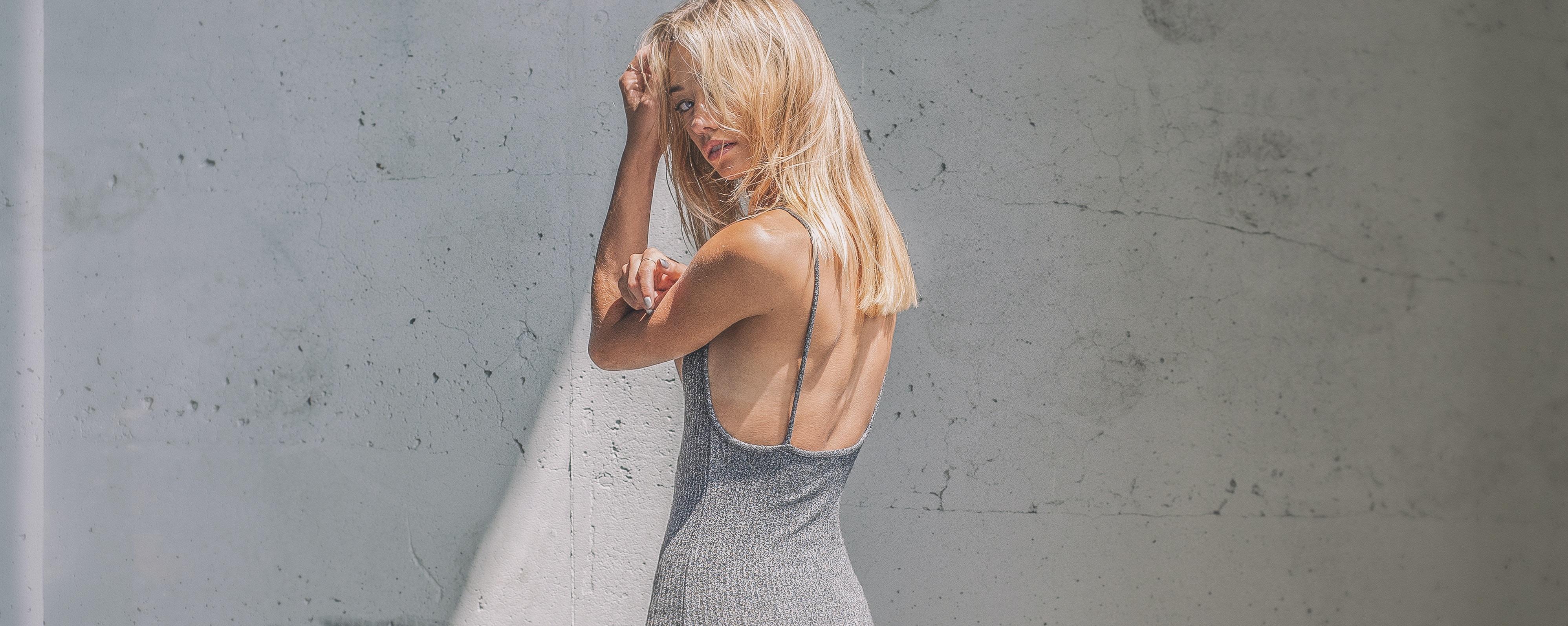 woman in gray sleeveless dress turn head on her left side