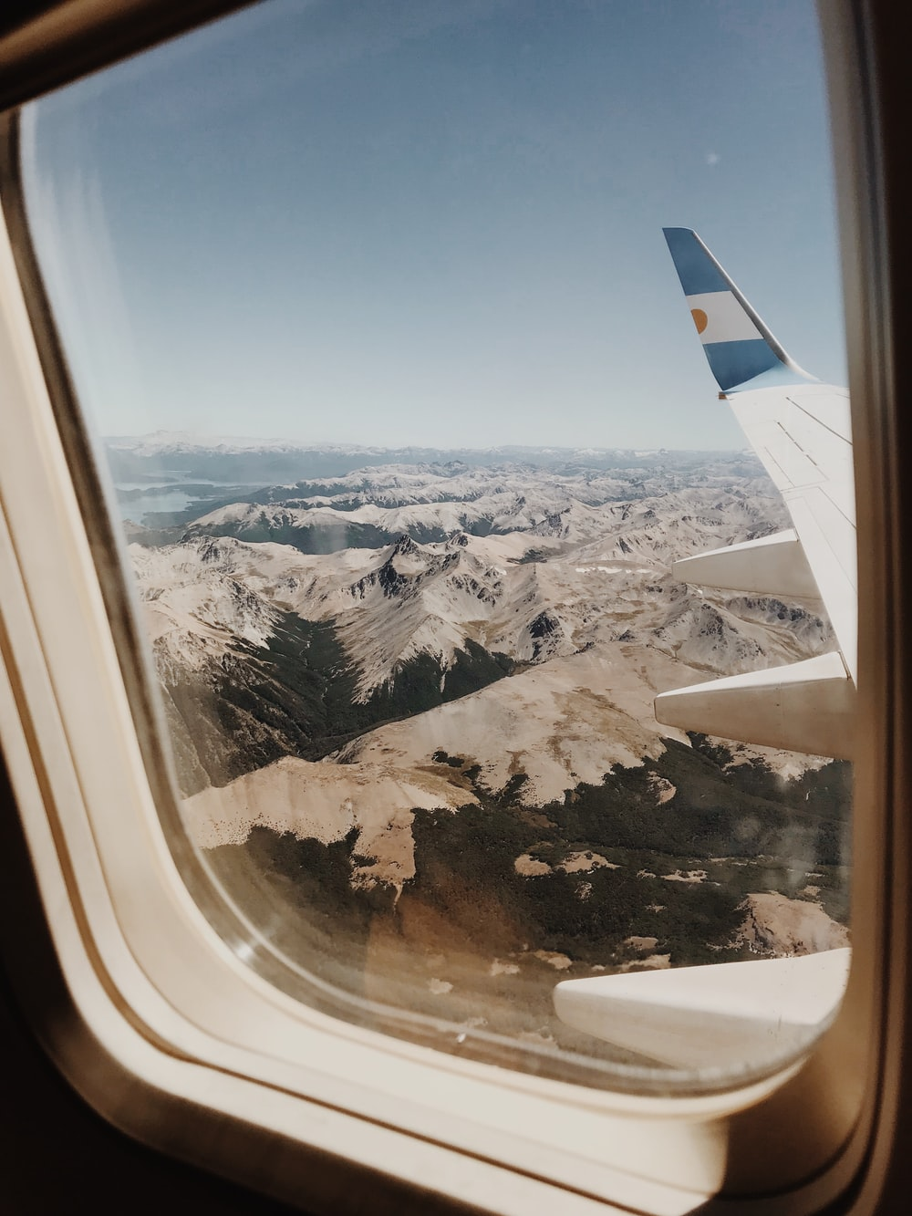 person taking picture of mountains inside airplane
