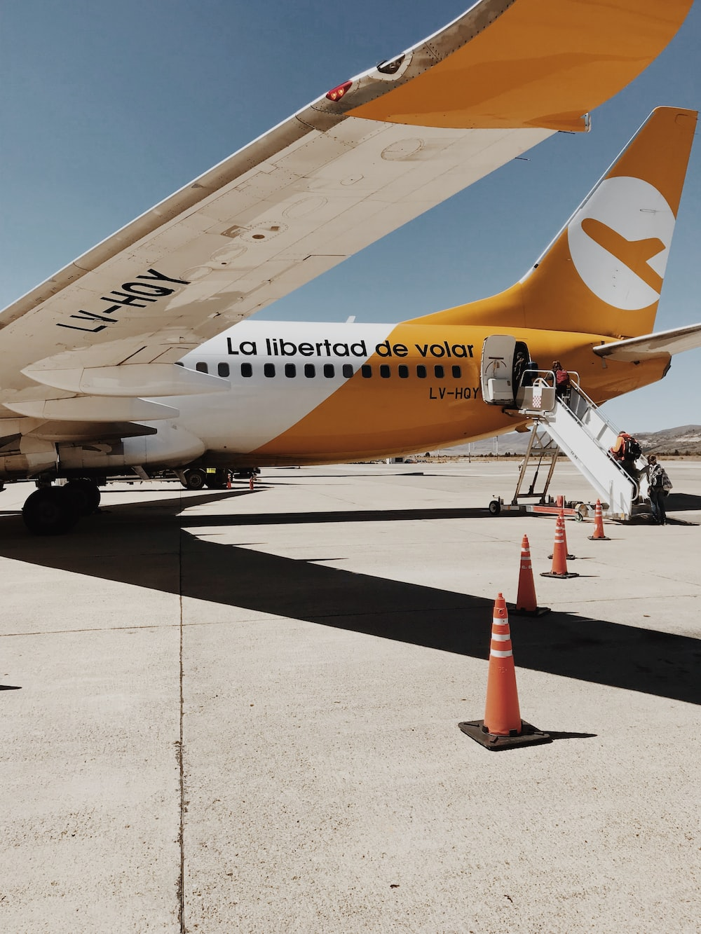traffic cones beside opened plane at airport during daytime