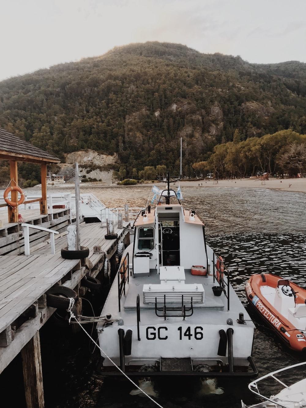 white yacht docking near mountain hill during daytime