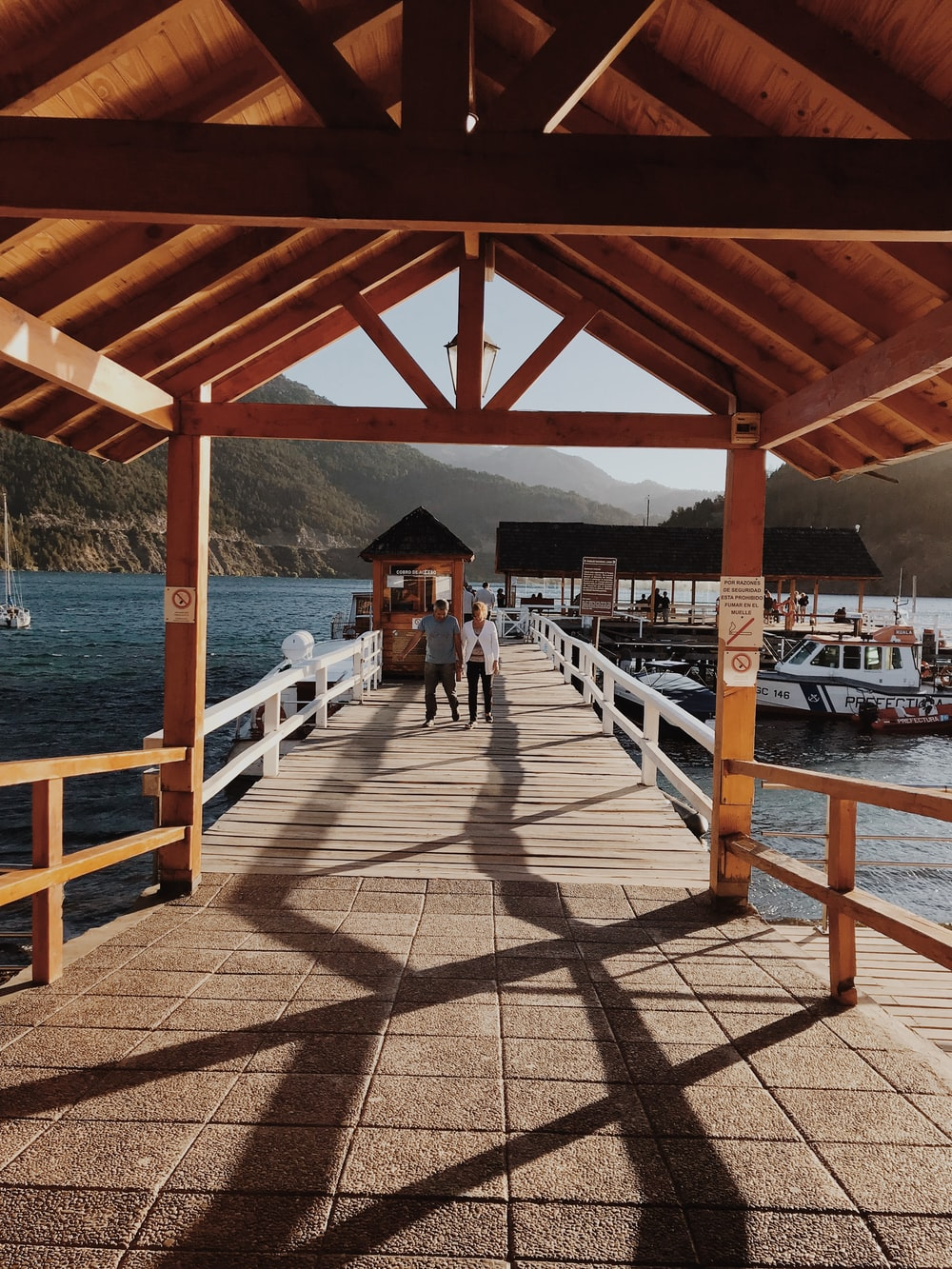 man and woman walks on dock during daytime