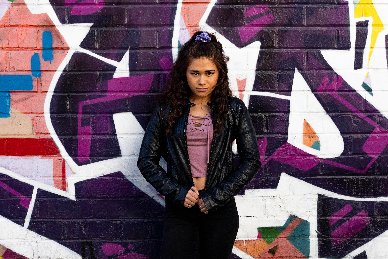woman standing beside graffiti wall