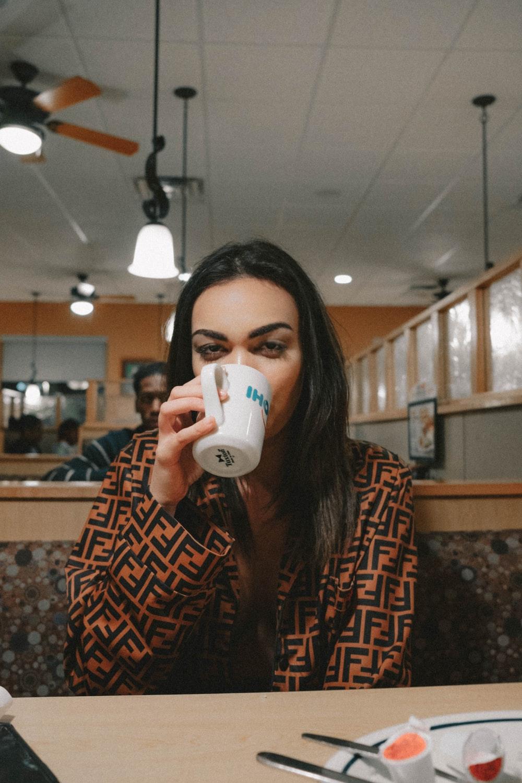 sitting woman drinking from white ceramic mug