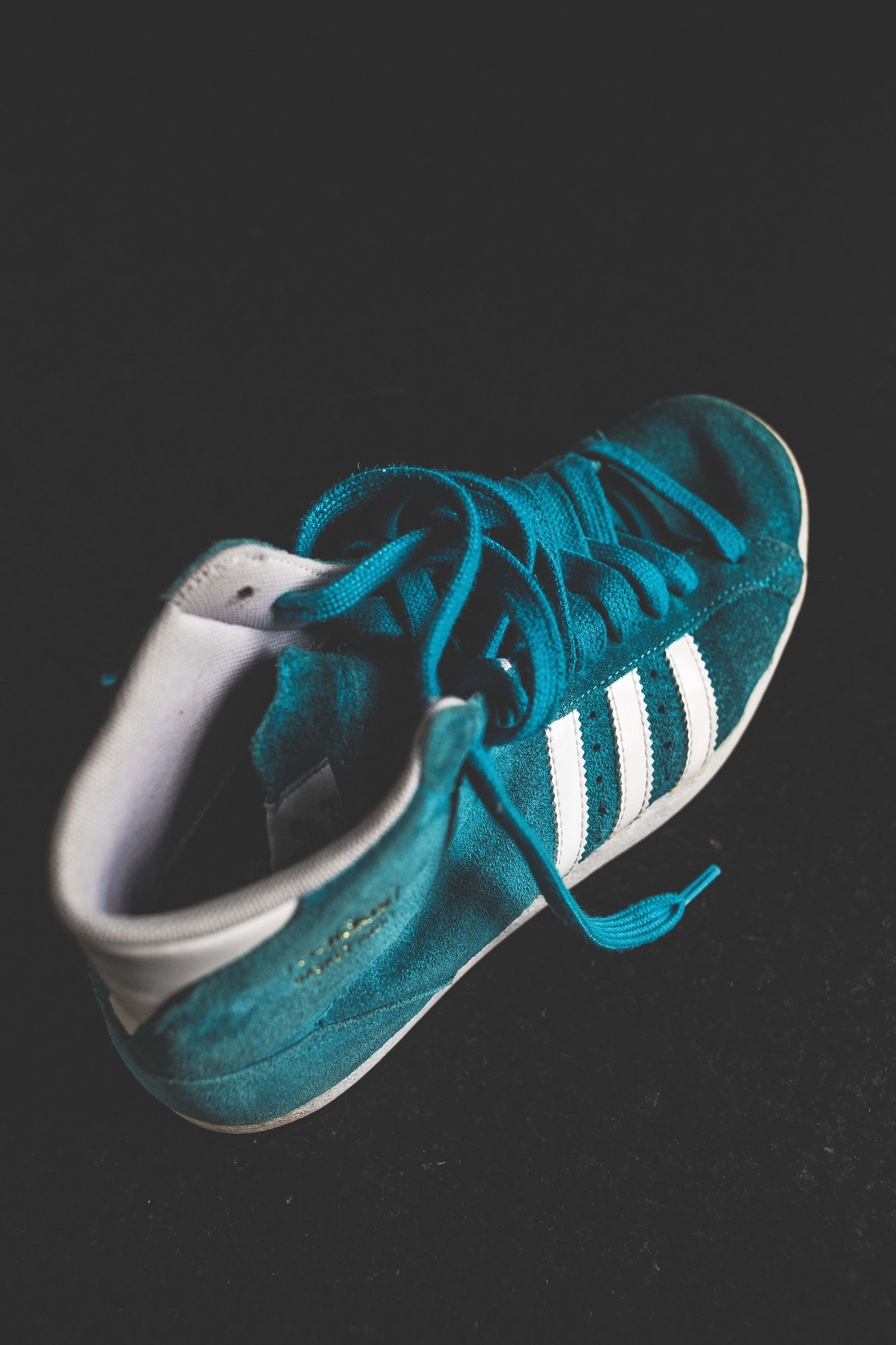 untied green and white Adidas high-top shoe