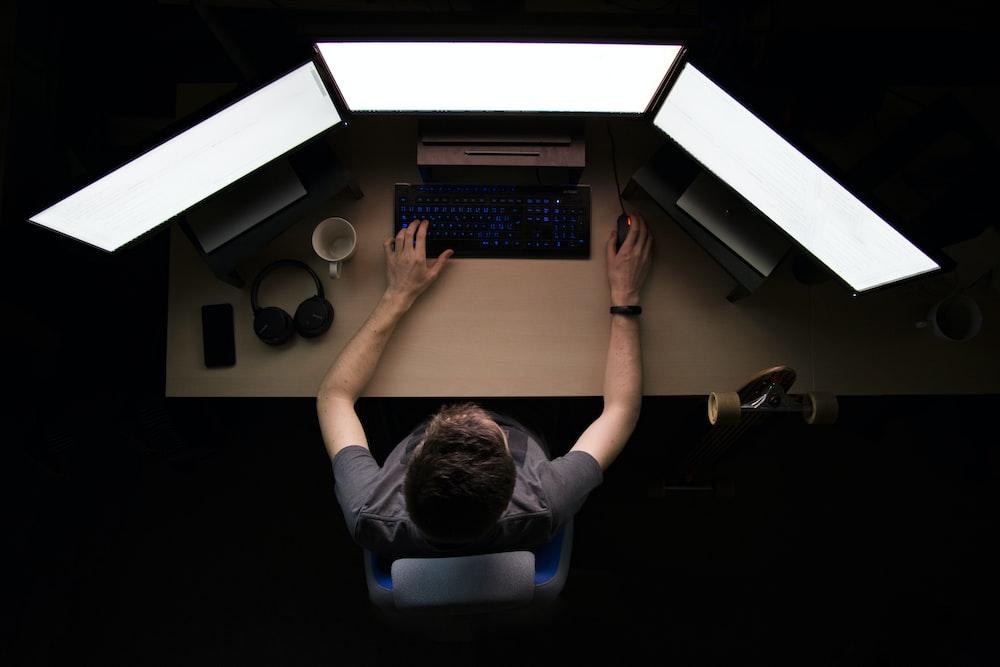 man facing three computer monitors while sitting