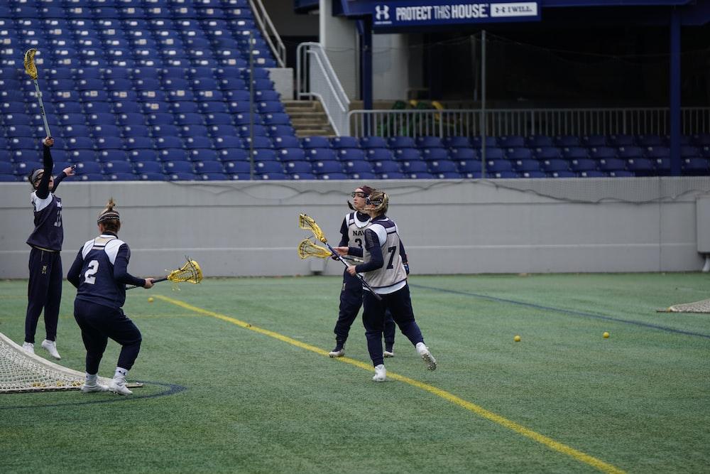 four women playing lacrosse during daytime